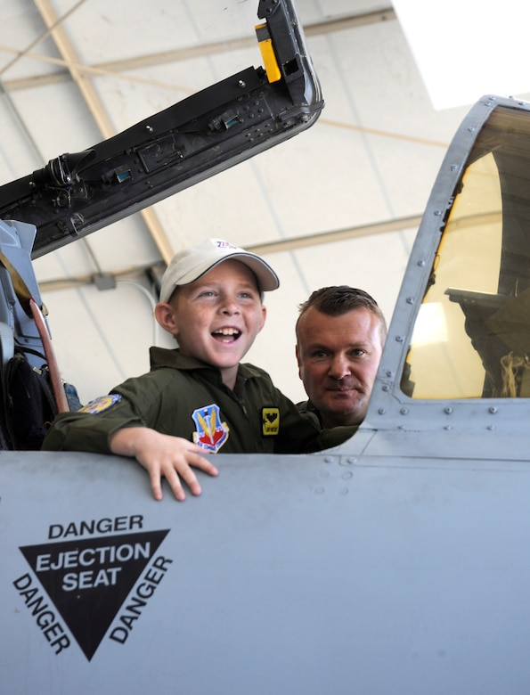 Eight-year-old Larry Ronstadt smiles as host pilot U.S. Air Force Maj. Richard Benda, 357th Fighter Squadron, explains the cockpit of the A-10 Thunderbolt II on Oct 25, 2012, during the Pilot for a Day event of Davis-Monthan Air Force Base, Ariz.  Larry was a Pilot for a Day for the 357th Fighter Squadron, and Major Benda is the Assistant Director of Operations for the 357 FS.   Pilot for a Day is a program which provides children with a terminal illness a day to visit the base and become an honorary pilot for one of the operational squadrons.  (U.S. Air Force photo by 1LT Susan Harrington/released)