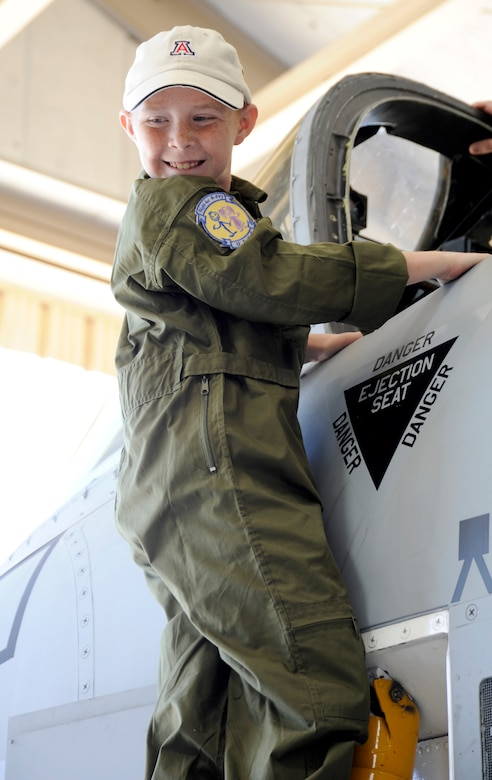 Eight-year-old Larry Ronstadt climbs into the cockpit of an A-10 Thunderbolt II static on Oct 25, 2012, during the Pilot for a Day event at Davis-Monthan Air Force Base, Ariz.  Pilot for a Day is a program which provides children with a terminal illness a day to visit the base and become an honorary pilot for one of the operational squadrons.  (U.S. Air Force photo by 1LT Susan Harrington/released)
