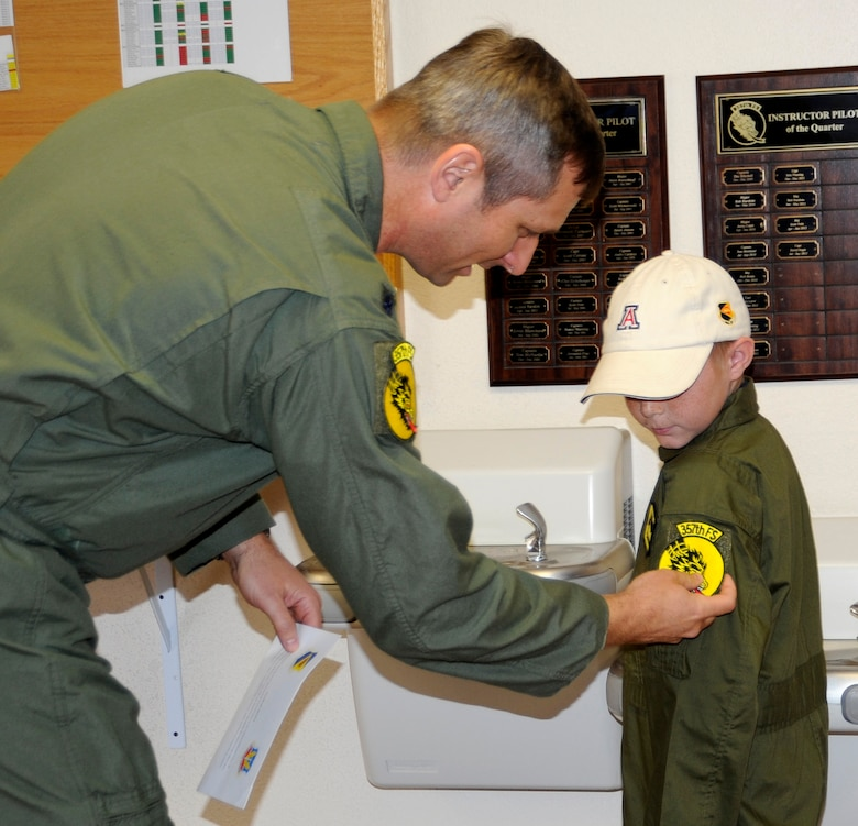 """U.S. Air Force Lt Col. John Gabriel, 357th Fighter Squadron commander, gives Larry Ronstadt the 357th Fighter Squadron patch just after administering the Pilot for a Day """"Oath of Office,"""" during the Pilot for a Day program at Davis-Monthan Air Force Base, Ariz.  Larry was an honorary 357th FS pilot here on Oct 25, 2012, where he, his father and grandfather toured the squadron, visited an A-10 static, an HH-60 static and the base Fire Department.  Larry is the eight-year-old son of Jeff and Tiana Ronstadt. (U.S. Air Force photo by 1LT Susan Harrington/released)"""