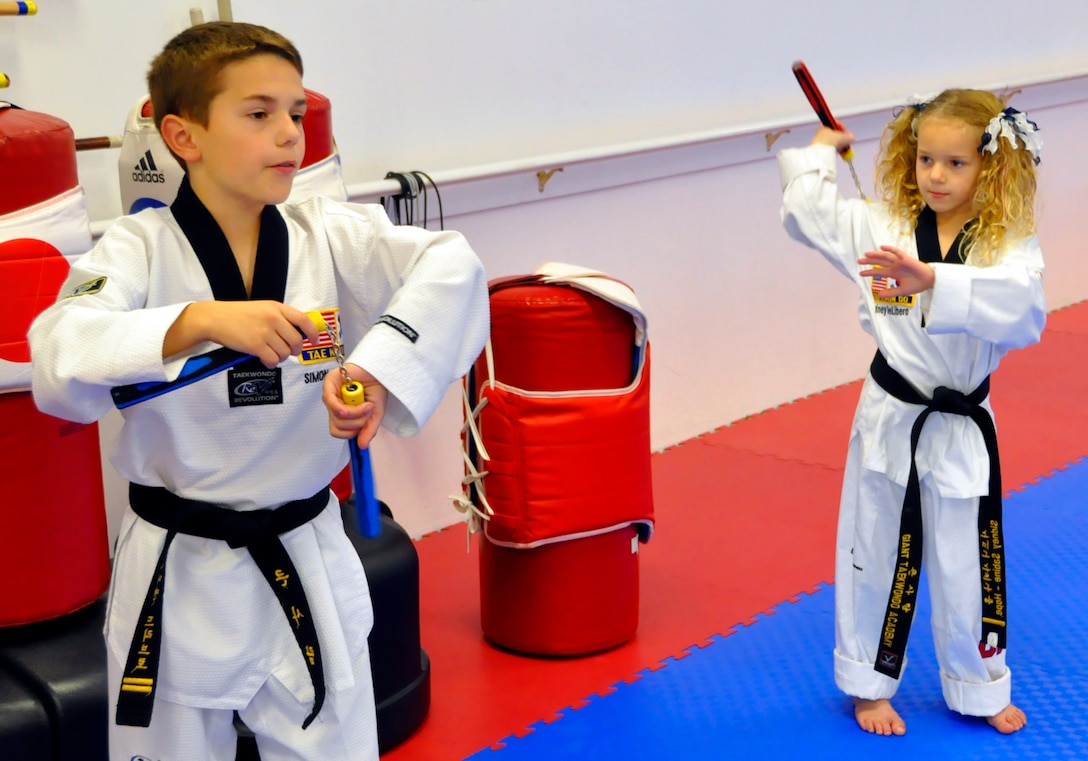 Simon DeLibero, a 446th Airlift Wing Reservist's son, practices nunchuck skills with his sister, Sidney, at a taekwondo school in Edgewood, Wash., Oct. 17. Activities like taekwondo helped Simon, a second-degree black belt, and his sister, a first-degree black belt, get through their father's military responsibilities away from home. (U.S. Air Force photo/Staff Sgt. Rachael Garneau)