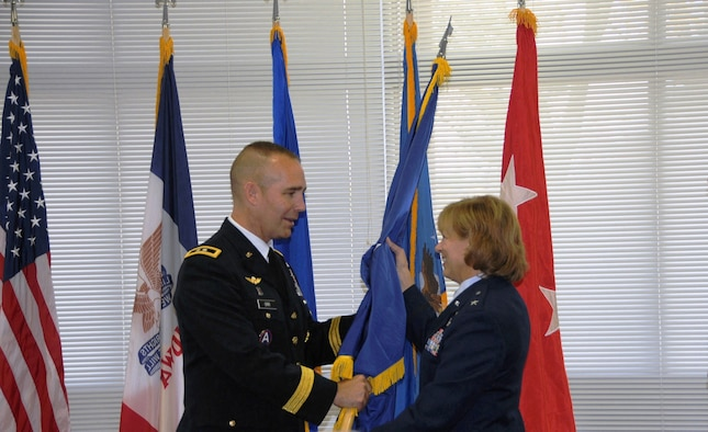 Maj. Gen. Tim Orr (left) Adjutant General of the Iowa National Guard, presents a General Officer flag to Brig. Gen. Jennifer Walter (right) at her promotion ceremony to Brigadier General on Oct. 14, 2012 at the 132nd Fighter Wing (132FW), Iowa Air National Guard, Des Moines, Iowa. Brig. Gen. Walter is the first female General Officer in the history of the Iowa Air National Guard. (US Air Force photo/Master Sgt Robert P. Shepherd)(Released)