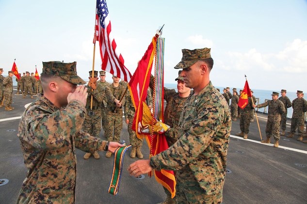 Lieutenant Col. John Wiener (right), commanding officer, Combat Logistics Battalion 15, 15th Marine Expeditionary Unit, accepts a unit citation in order to rededicate the unit's battle colors during their 25th birthday aboard the USS Rushmore, Oct. 15. The 15th MEU along with the Peleliu Amphibious Ready Group, which includes the USS Rushmore, USS Peleliu and USS Green Bay, is currently deployed to the Western Pacific.