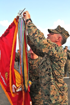 Lieutenant Col. John Wiener (right), commanding officer, Combat Logistics Battalion 15, 15th Marine Expeditionary Unit, redecorates the unit's battle colors during their 25th birthday aboard the USS Rushmore, Oct. 15. The 15th MEU along with the Peleliu Amphibious Ready Group, which includes the USS Rushmore, USS Peleliu and USS Green Bay, is currently deployed to the Western Pacific.