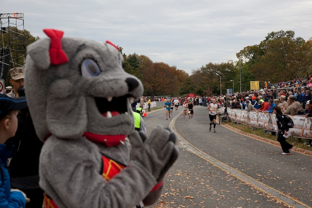 Molly, a volunteer mascot, cheers on runners approaching the finish line during the 37th Marine Corps Marathon Oct. 28. The 37th MCM enjoyed its largest number of starters to date with 23,864 people from across the world, who came to reach their 26.2-mile goal beating Hurricane Sandy to the finish line.