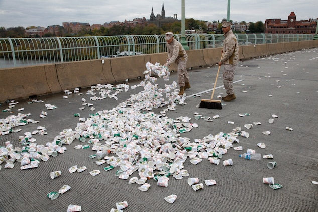 Marine volunteers clean the Francis Scott Key Bridge water point after the last runner passed through during the 37th Marine Corps Marathon Oct. 28. Volunteers distributed 850,000 cups of water and 30,000 bottles of Gatorade during the 26.2-mile course.