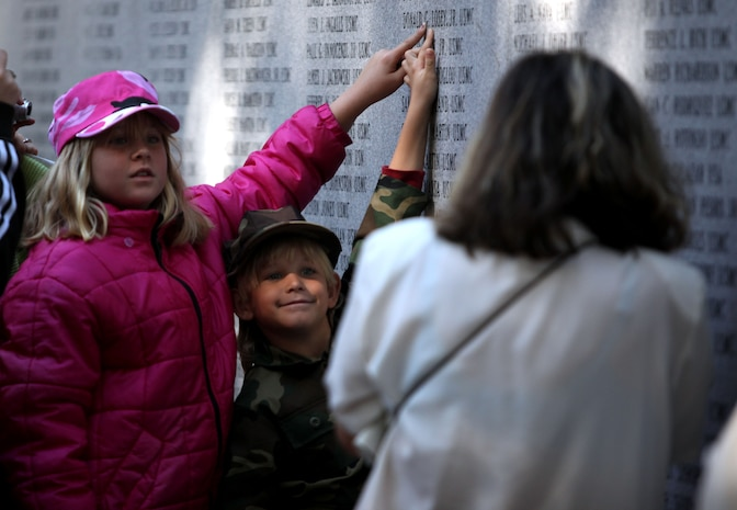 A boy and a girl point to the name of a fallen Marine during the Beirut Memorial Service Ceremony in Jacksonville, N.C., Oct. 23. Names are inscribed on the wall of the Beirut Memorial to honor the service members who died the Beirut attack in 1983.