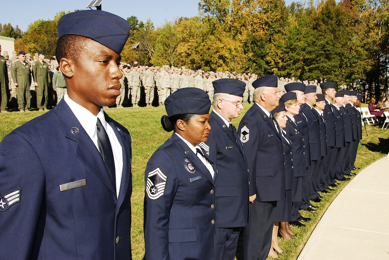 """Family members, including those of recently honored aerial fire fighters and more than a thousand airmen of Charlotte's 145th Airlift Wing, North Carolina Air National Guard attend an annual memorial ceremony as a way to remember all airmen who have died in the year prior, whether a current or past member. Following a flyover of three C-130 Hercules, the aircraft used by the wing to accomplish its missions, the names are pronounced of any Air Guard member who has deceased over the last twelve months to a bagpipe rendition of """"Amazing Grace,"""" the formation of airmen at attention for a twenty-one gun salute, then a bugler performing """"Taps,"""" and the laying of a wreath in honor and remembrance of those who have passed.  (National Guard photos by Tech Sgt. Rich Kerner, 145th Public Affairs)"""