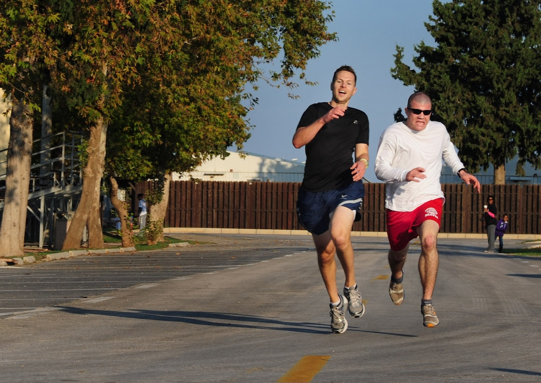 Chad Gregory, 39th Security Forces Squadron, right, and Jason Clute, 39th Force Support Squadron, race to the finish line during the Triple Ribbon 5k run Oct. 27, 2012, at Incirlik Air Base, Turkey. Gregory and Clute tied for first place with a final run time of 18 minutes, 34 seconds. (U.S. Air Force photo by Senior Airman Anthony Sanchelli/Released)