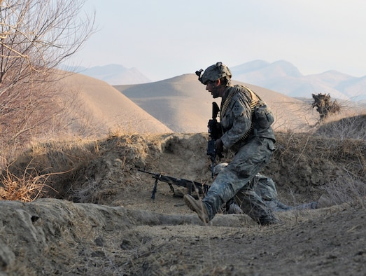 U.S. Army Sgt. Timothy Cooper and other Soldiers from White Platoon, Bulldog Troop, 7th Squadron, 10th Cavalry Regiment, take cover as they receive accurate small-arms fire on a riverbed near Combat Outpost Delorean, Bala Murghab, Badghis Province, Afghanistan Jan. 9, 2011. The patrol consisted of Soldiers deployed from 1st Brigade, 4th Infantry Division out of Fort Carson, Colo., Afghan National Army soldiers from Bala Murghab, two Tactical Air Control Party Airmen from Fort Hood, Texas, and Fort Bragg, N.C., a Navy Reserve videographer, and an Air Force photojournalist from Royal Air Force Mildenhall, England. (U.S. Air Force photo/Master Sgt. Kevin Wallace/RELEASED)