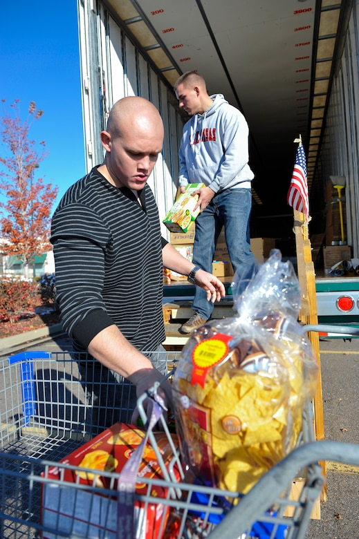DENVER -- Senior Airmen James Caldwell, left, and Torrey Erbes, both 460th Security Forces Squadron armorers, unload a cart of donations during a Fill the Mayflower food drive Oct. 26, 2012, at a local grocery store. The Mayflower moving truck will bring the donations to Buckley Air Force Base, Colo., where volunteers will sort the contents into care packages for junior enlisted service members in need this Thanksgiving. (U.S. Air Force photo by Staff Sgt. Kathrine McDowell)