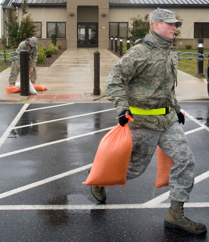 Airman 1st Class Richard Stratton, from the 436th Civil Engineer Squadron, and Senior Airman Robert Fitch, from the 436th Aerial Port Squadron, collect sandbags from outside of building 502 Oct. 30, 2012, at Dover Air Force Base, Del. The sandbags were placed at entrances around the base in preparation for Hurricane Sandy. (U.S. Air Force photo by Adrian R. Rowan)