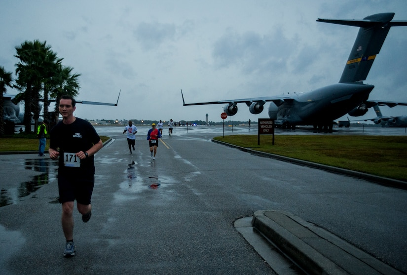 Participants run between a pair of C-17s during the fourth annual Run the Runway 5K event honoring retired Brig. Gen. Thomas Mikolajcik Oct. 27, 2012, at Joint Base Charleston - Air Base, S.C. The 437th Airlift Wing hosted the event which was open to all military, Department of Defense civilians and the local community. (U.S. Air Force photo/ Airman 1st Class George Goslin)