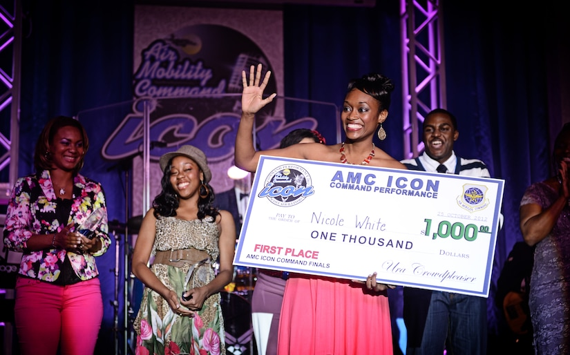 1Lt. Nicole White, from Scott Air Force Base, accepts her first place award after performing for a crowd of more than 200 at the Scott Air Force Base club Oct. 25, 2012. Ten performers participated in the 2012 AMC Icon, a contest similar to the famed American Idol in which contestants competed for cash prizes and a spot to perform in the U.S. Air Force Tops in Blue group. 1Lt. Nicole White took the top prize with Staff Sgt. Tiry Crane as the runner up and TSgt Doug Boren in third place. (U.S. Air Force photo/ Staff Sgt. Ryan Crane)