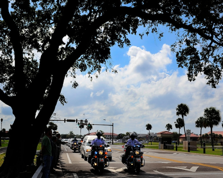 Hillsborough County Sheriff's department motorcade escort Spc. Brittany B. Gordon's procession off of MacDill Air Force Base, Fla., while service member and civilians pay their respects by lining the streets Oct 24, 2012. Gordon died of wounds suffered when enemy forces attacked her unit with an improvised explosive device while supporting Operation Enduring Freedom in Kandahar, Afghanistan. Gordon was assigned to the 572nd Military Intelligence Company, 2nd Stryker Brigade Combat Team, 2nd Infantry Division at Joint Base Lewis-McChord, Wash. (U.S. Air Force photo by Staff Sgt. Angela Ruiz/Released)