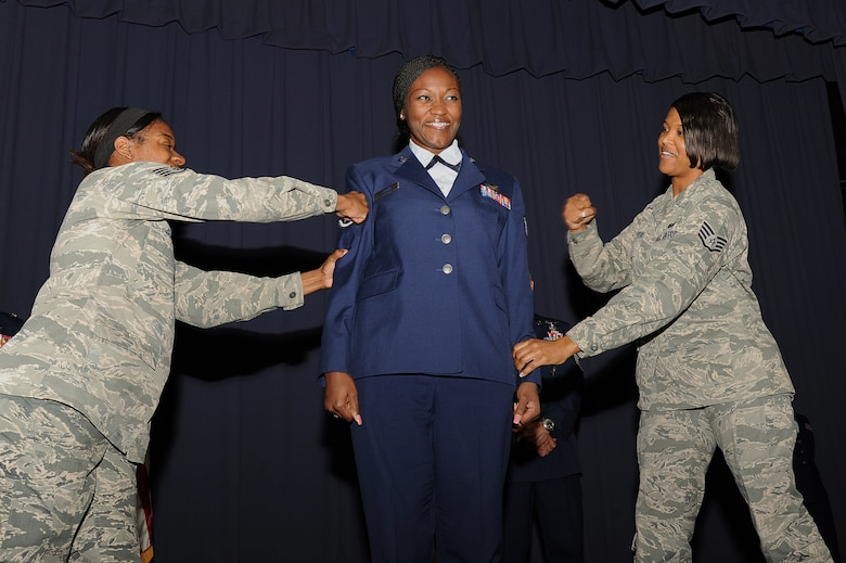 U.S. Air Force Staff Sgt. Kimberly Jones, a career development specialist with 1st Special Operations Force Support Squadron, withstands the punches that mark her transition to staff sergeant during an NCO recognition ceremony at the King Auditorium on Hurlburt Field, Fla., Oct. 30, 2012. Part of the NCO recognition ceremony is the reading of the NCO Charge, which lays out the new responsibilities as staff sergeants. (U.S. Air Force Photo/Airman 1st Class Michelle Vickers)
