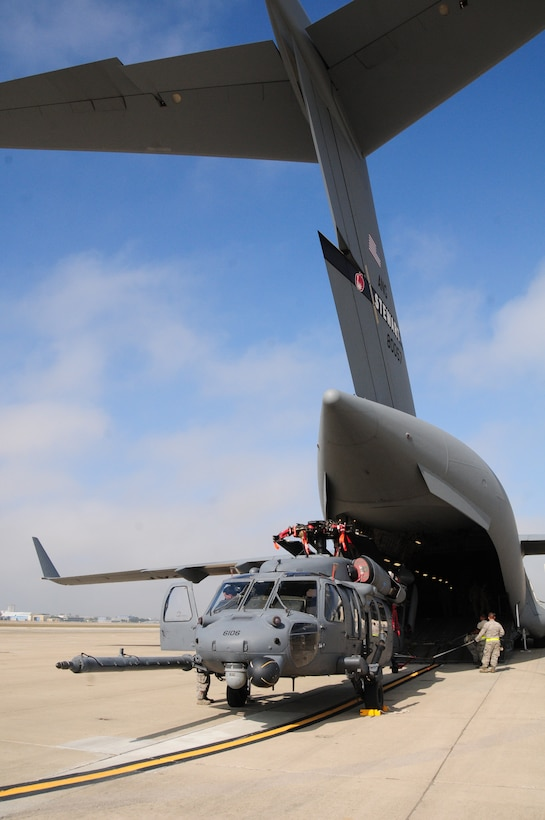An HH60G Pave Hawk helicopter from the 129th Rescue Squadron is loaded into a C17 Globemaster III at Moffett Federal Airfield, Calif., Oct 29, 2012.  More than 100 California Air National Guardsmen from the 129th Rescue Wing  prepare to mobilize to the East Coast to assist with Hurricane Sandy rescue efforts.  Two MC-130P Combat Shadow aircraft, two HH-60G Pave Hawk rescue helicopters and two Guardian Angel Pararescue teams mobilized to the East Coast to provide life-saving rescue capabilities to those in need in the aftermath of Hurricane Sandy.  (Air National Guard photo by Tech. Sgt. Ray Aquino/RELEASED)