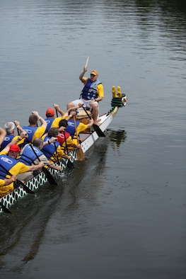 The Air War College team paddles to the start line for their first race of the Montgomery Dragon Boat Festival Saturday.