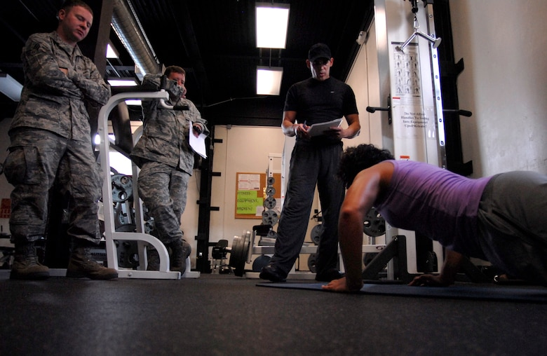 125th Fighter Wing Medical Service Journeyman, Staff Sgt. Mariam Abdallah, performs pushups as 125th Fighter Wing Health Promotions Officer, Captain Jesus Garcia (second from right) keeps count, as, 125th Fighter Wing, Jacksonville, Fla, August 18, 2012.  (looking on are 125th Fighter Wing Chaplain's Assistant, Senior Airman Winter and 125th Fighter Wing Chaplain First Lt. John Williams) (Air National Guard photo by MSgt. Shelley Gill)