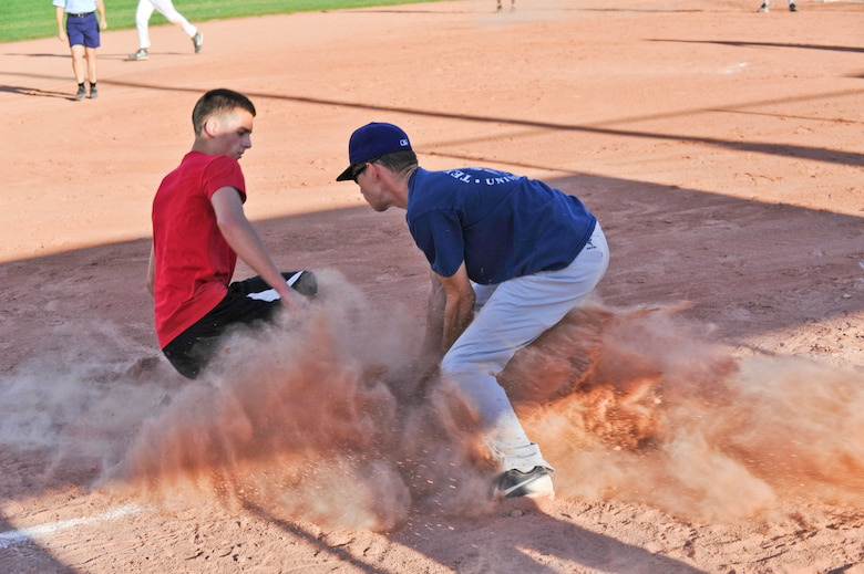 BUCKLEY AIR FORCE BASE, Colo. – Wade Bishop, left, member of SBIR of the 2nd Space Warning Squadron slides into third base safely as Corey Dorsey of the 566th Intelligence Squadron attempts the tag during a Buckley Intramural Softball Championship game Sept. 4, 2012. SBIRS, , won back-to-back games against the 566 IS making them the 2012 intramural softball base champions. (U.S. Air Force photo by Senior Airman Christopher Gross)