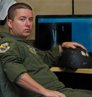 ALTUS AIR FORCE BASE, Okla. – Master Sgt. Lee Adkins, Headquarters Air Mobility Command KC-135 Air Training Squadron Quality Assurance manager, poses with his helmet in front of an X-ray photo of his right arm, July 24, 2012. Adkins was in a near-fatal motorcycle accident Jan. 15, 2012 and recently returned to flying status. Since his accident Adkins keeps his helmet from the wreck on his desk as a conversation starter, to talk about the importance of wearing personal protective equipment. (U.S. Air Force photo by Airman 1st Class Kenneth W. Norman / Released / 97th Air Mobility Wing Public Affairs)