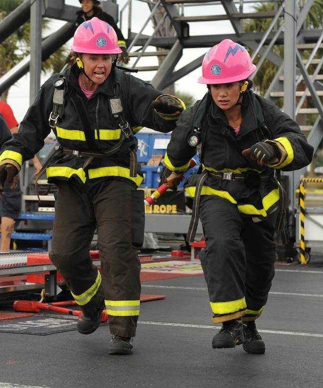 Elaine Perkins, right, takes the baton from Stacey Billapando during the World Firefighter Combat Challenge in Myrtle Beach, S.C., Nov. 16, 2011. Perkins, a native of Honolulu and station captain for Fire Station 3 at the Air Force Academy in Colorado Springs, Colo., was named the 2011 National Image, Inc., Meritorious Service Award winner. Billapando is a firefighter with the Colorado Springs Fire Department. Perkins, Billapando, Andrea Caraway and Senior Airman Jessica Condon comprised the now-retired Fire Fembots team, which set a world record time for women's relay in 2009. (U.S. Air Force photo/John Van Winkle)