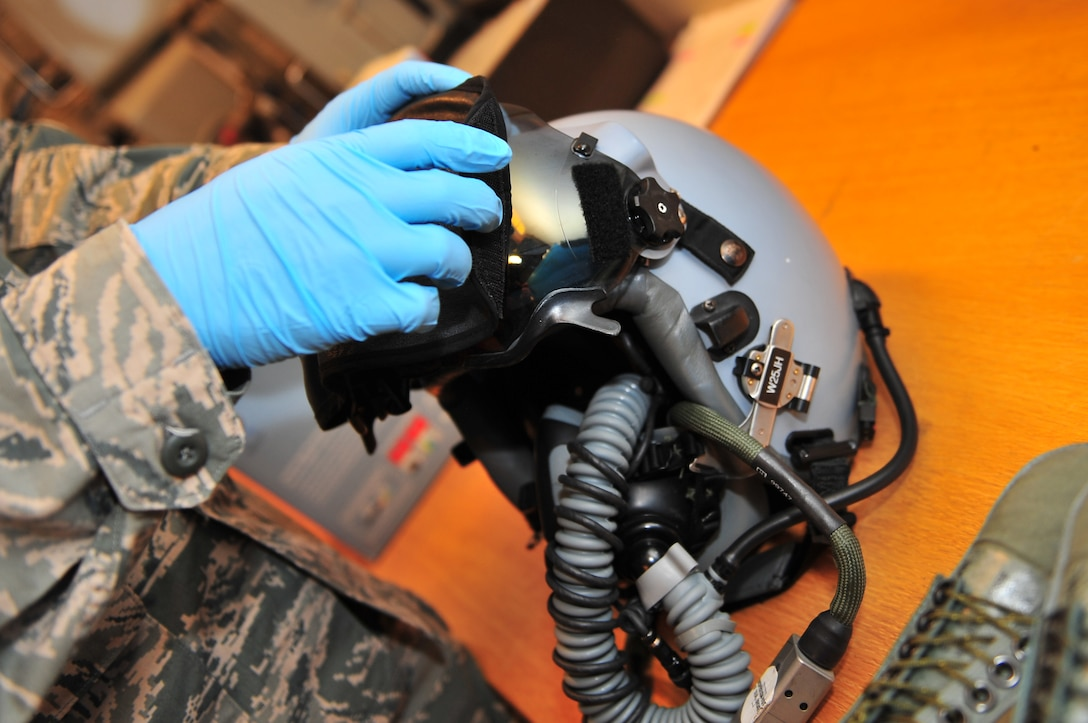 KALLAX AIR BASE, Sweden -- Airman 1st Class Niall Spradley, 52nd Operations Support Squadron, attaches a visor to a heads up display on a pilot's helmet here Sept. 4 before flight in support of the Nordic Air Meet 2012. The multinational training exercise brought together more than 50 aircraft from the U.S., Great Britain, Denmark, Finland, Switzerland and Sweden to participate in tactical role-playing training missions. The three week exercise enabled the different nations to exchange aerial tactics and capabilities to improve combat power effectiveness in solo and joint environments while building and strengthening international partnerships. (U.S. Air Force Photo by Airman 1st Class Dillon Davis/Released)