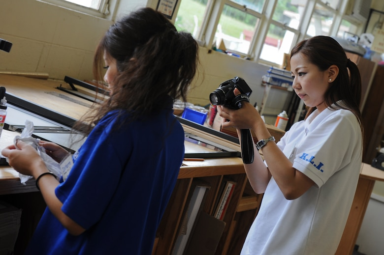 Minayo Tsuhako (right), a Kadena Language Institute student, takes a photo of Yui Makawa (left), also a KLI student, during her internship at the 18th Wing Public Affairs office on Kadena Air Base, Japan, Sept. 4, 2012. Tsuhako is part of the KLI internship program which gives members of the class a chance to work at places around Kadena for a month in preparation for attending schools abroad. (U.S. Air Force photo/Airman 1st Class Brooke P. Beers)