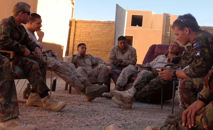Marines and New Zealand Army soldiers, also known as Kiwis, sit in a circle on worn-out couches, chairs and benches as they wait for their next scenario in their counter insurgency exercise at Range 220A, June 20. The Marines and Kiwis made strong bonds during their down time as they found out just how much they had in common.