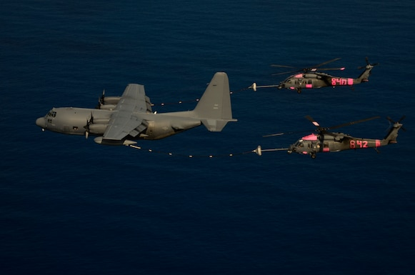 An MC-130P Combat Shadow airplane refuels two HH-60G Pave Hawk rescue helicopters, still marked pink from supporting Northern California wildfire operations last week, over the Pacific Ocean during a rescue mission on September 5, 2012.  The aircraft, all from the 129th Rescue Wing, were used in a joint operation with the U.S. Coast Guard to rescue two injured Ecuadorian fishermen. (Air National Guard photo by Airman 1st Class John D. Pharr III)