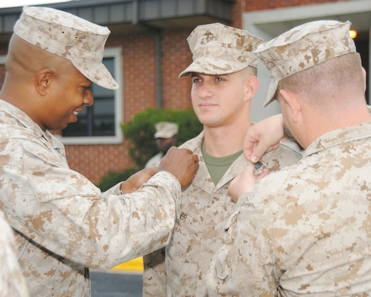 Gunnery Sgt. Morgon Latimore, left, and Sgt. Brandon Wilson, right, pin chevrons on Sgt. Edward Peifer during his meritorious promotion Aug. 21 in front of Building 3500, here.