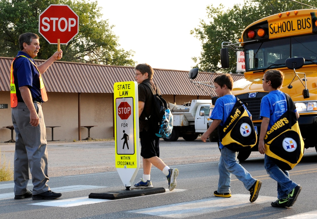 Rick Hatfield, Vandenberg Elementary School Title 1 Math and Reading teacher and volunteer crossing guard, stops traffic while students walk across Liberty Boulevard in Box Elder, S.D., Sept. 6, 2012. Douglas School District officials have posted crossing guards at different intersections around their schools due to the increase in vehicle and pedestrian traffic as a result of the change in bussing availability and housing accommodations for Ellsworth Air Force Base residents. (U.S. Air Force photo by Airman Ashley J. Woolridge/Released)