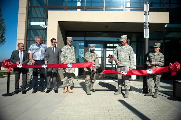 SPANGDAHLEM AIR BASE, Germany – Col. David Julazadeh, 52nd Fighter Wing commander, cuts the ribbon at a ribbon cutting ceremony, along with leadership from the base, U.S. Army Corp of Engineers, and the local community here Sept. 7. The $30.1 million clinic officially opens Sept. 10 and includes a larger parking lot, a 75,000 square foot building, 23 exam rooms, 218 medical professionals, and new medical equipment and furniture.  (U.S. Air Force photo by Airmen 1st Class Gustavo Castillo/Released)