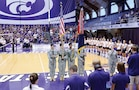 From left to right, Spc. Joseph Vera, Sgt. Bradley Kelly, Spc. Carlos Martinez and Pfc. Eric Rollins, all Soldiers with the CAB, present the colors, while Sgt. Tiana Navarro, 1st Inf. Div. Band, sings the national anthem at K-State's Volleyball Military Appreciation Night Aug. 25 at Ahearn Field House.  Photo by: Capt. Drew Cochran, CAB.