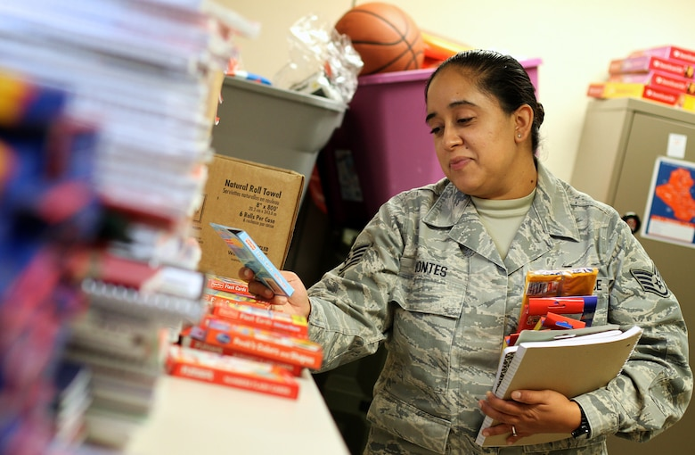 Staff Sgt. Francisca Montes, Non-Commisioned Officer in Charge, Personnel Readiness, looks over the donated school supplies in the 932nd Airlift Wing Family Readiness office.  Montes was picking up suppplies for her children.  (U.S. Air Force photo/Tech. Sgt. Christopher Parr)