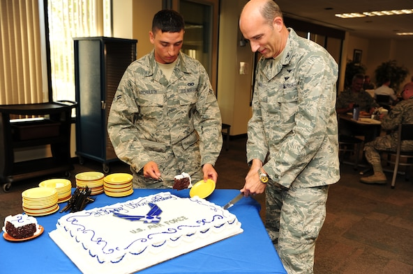 U.S. Air Force Col. Jeffrey T. Mineo and U.S. Air Force Airman 1st Class Abram Archuleta, the youngest Airman in the 310th Space Wing, celebrate the Air Force's birthday, as well as the anniversaries of Air Force Space Command and the 310th Space Wing, with a cake cutting ceremony on Schriever Air Force Base, Colo., Sept. 8. (U.S. Air Force photo by Tech. Sgt. Nicholas B. Ontiveros/Released)
