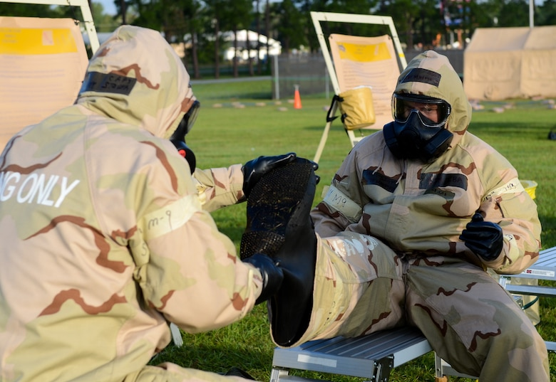U.S. Air Force Airmen assist one another while processing through a contamination control area during an operational readiness inspection at Robins Air Force Base, Ga., Sept. 6, 2012. More than 500 Airmen simulated a deployment that tested basic knowledge such as self-aid and buddy care, and chemical, biological, radioactive nuclear and explosive responses. Portions of this image have been blurred for security reasons. (National Guard photo by Master Sgt. Roger Parsons/Released)