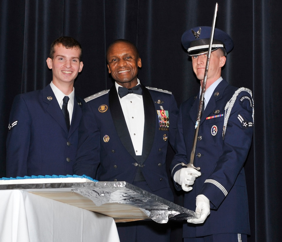 Lt. Gen. Darren McDew, commander of 18th Air Force, poses with Airman 1st Class Christopher Sims, left, the youngest Airman in attendance, and Airman 1st Class David Brannum, Team Dover honor guard member, after cutting the birthday cake at the Air Force Ball Sep. 7, 2012, at Dover Downs in Dover, Del. The cutting of the cake was part of the celebration commemorating the Air Force's 65th birthday. (U.S. Air Force photo by Tech. Sgt. Chuck Walker)