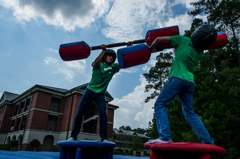 """Seaman Dixon Andrew and Seaman Alex Harbeson, Naval Nuclear Power Training Command Electrician's Mate students, fight with pugil sticks during the """"Barracks Bash"""" celebration after the Day of Caring Sept. 7, 2012, at Joint Base Charleston - Weapons Station, S.C. The Day of Caring, organized locally by the Trident United Way, saw more than 8,500 volunteers working on more than 300 projects around the Lowcountry. (U.S. Air Force photo by Airman 1st Class George Goslin)"""