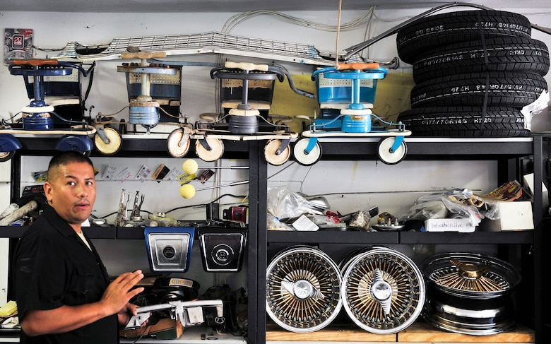 "Staff Sgt. Raul Chavez shows off items he is working on and has completed in the past in his ""man cave"" one of which is on display, a 1960 Murray tricycle. (U.S. Air Force photo/ Staff Sgt. Stephenie Wade)"