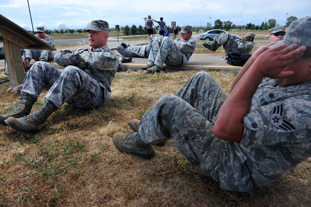 BUCKLEY AIR FORCE BASE, Colo. – Defenders of the 460th Security Forces Squadron performs sit-ups at the first station of a 5K rucksack march Sept. 11, 2012. Participants crunched 11 sit-ups at the first station of the march to remember American Airlines Flight 11 that crashed into the north tower of the World Trade Center. Ten additional stations lined the march where participants performed exercises corresponding to facts about the events of 9/11. (U.S. Air Force photo by Airman 1st Class Darryl Bolden Jr.)