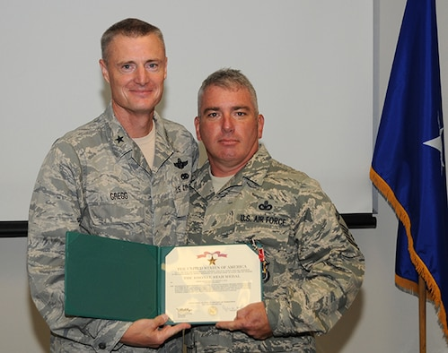 "Brig. Gen. Steven Gregg, Commander of the Oregon Air National Guard, presents the Bronze Star to Senior Master Sergeant Timothy Lear, 142nd Security Forces Squadron, on Aug. 3, 2012.  Lear received the medal for ""extraordinary leadership"" while being assigned to the 966th Air Expeditionary Squadron, Baghram Air Base, Afghanistan.  (U.S. Air Force Photograph by Master Sgt. Shelly Ball, 142nd Fighter Wing Public Affairs)"