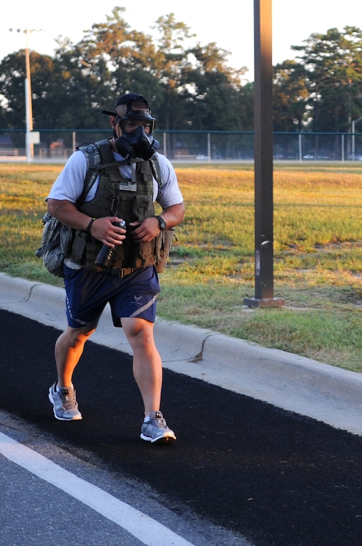 U.S. Air Force Staff Sgt. Chana Lawlor, 4th Logistics Readiness Squadron traffic management office representative, marches while carrying a ruck sack and wearing a gas mask during the 9/11 Remembrance Run on Seymour Johnson Air Force Base, N.C., Sept. 12, 2012. Lawlor marched more than four miles wearing approximately 80 pounds of gear to show his respect for those lost in the 9/11 attacks. (U.S. Air Force photo/Airman 1st Class Aubrey Robinson/Released)