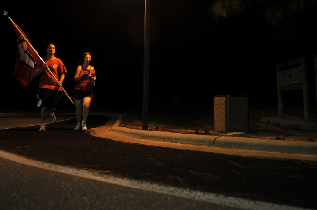 U.S. Air Force Senior Airman Shawn Patterson, 4th Civil Engineer Squadron driver operator, and his wife, Ginger, run with the 9/11 Remembrance Flag during the 24-hour run on Seymour Johnson Air Force Base, N.C., Sept. 11, 2012. Many members of Team Seymour ran to pay tribute to those lost in the 9/11 attacks. (U.S. Air Force photo/Airman 1st Class Aubrey Robinson/Released)