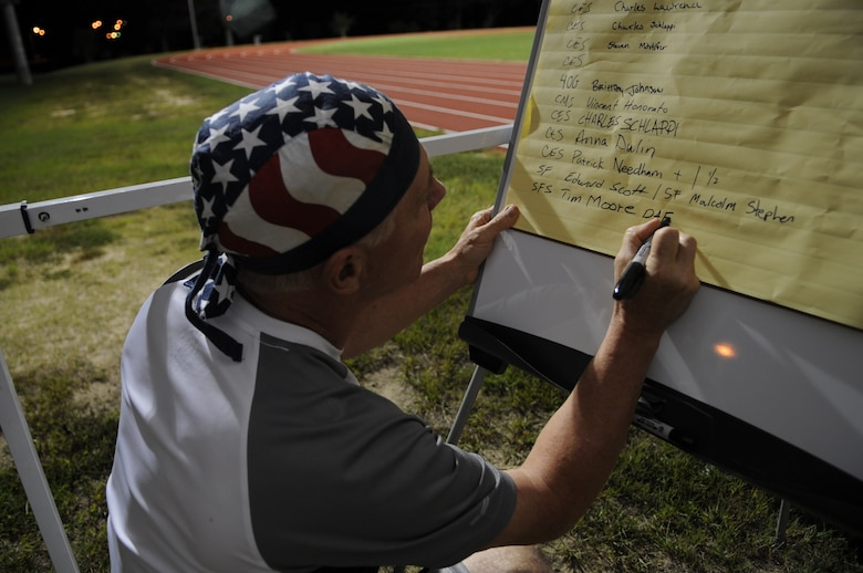 Tim Moore, 4th Security Forces Squadron gate guard, writes his name on a participant list during the 9/11 Remembrance Run on Seymour Johnson Air Force Base, N.C., Sept. 11, 2012. Many people signed up to run a one hour block of the 24-hour event, which paid tribute to those lost in the 9/11 attacks. (U.S. Air Force photo/Airman 1st Class Aubrey Robinson/Released)