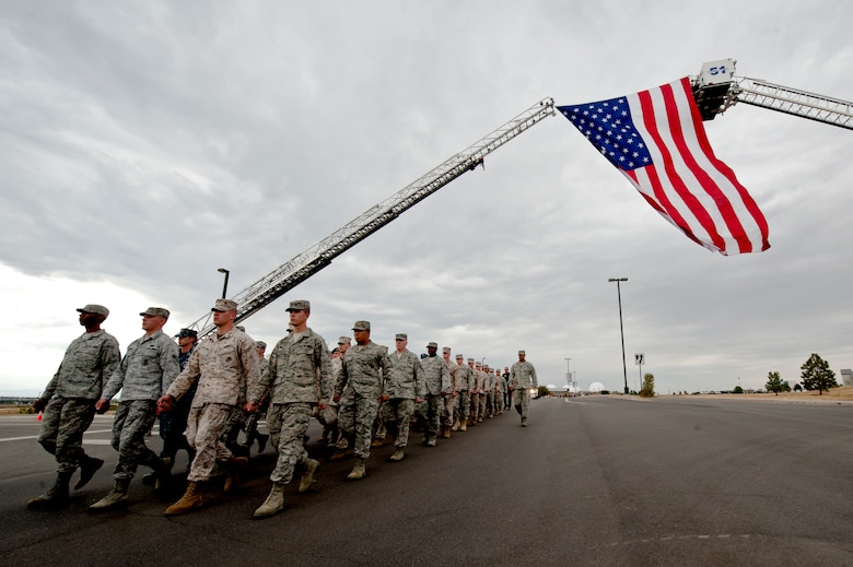 BUCKLEY AIR FORCE BASE, Colo. – Members of Team Buckley and the Aurora Fire Department march in remembrance of the 9/11 attacks Sept. 11, 2012. This march was the beginning of the remembrance ceremony held at the 460th Space Wing headquarters honoring those who died in New York City 11 years ago. (U.S. Air Force photo by Airman 1st Class Phillip Houk)