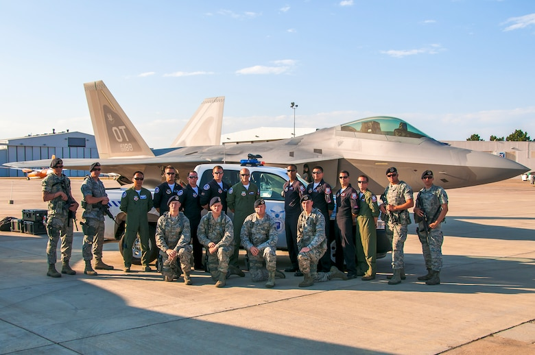 BROOMFIELD, Colo. -- Members of the 460th Security Forces Squadron pose with the F-22 Raptor Demonstration Team from Holloman Air Force Base, N.M., during the Rocky Mountain Airshow held the last weekend in August at the Rocky Mountain Metropolitan Airport. Eight 460th SFS Airmen were selected to provide around-the-clock security for the F-22 aircraft Aug. 23-27. (Photo by Scott E. Wolff)