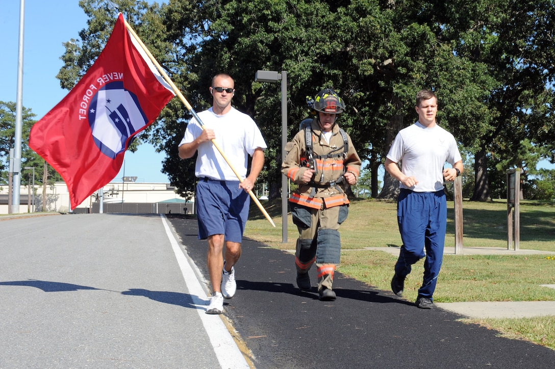 From left, U.S. Air Force Senior Airman Daniel Gough, 4th Civil Engineer Squadron fire inspector, Brent Collins, 4th CES fire captain, and Senior Airman Leland Soper, 4th Security Forces Squadron force protector, run around the 2-mile track on Seymour Johnson Air Force Base, N.C., Sept. 11, 2012. Seymour Johnson personnel performed a 24-hour run in honor of those killed in the 9/11 attacks. (U.S. Air Force photo/Airman 1st Class John Nieves Camacho/Released)