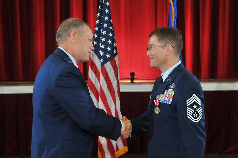 JOINT BASE SAN ANTONIO–LACKLAND, Texas -- Brig. Gen. Kevin Wooton, Air Force Space Command Communications and Information director, congratulates Chief Master Sgt. Mark Renninger, the former 67th Network Warfare Wing command chief master sergeant, during his retirement ceremony at Arnold Hall here, Sept. 5. Renninger retired after 30 years of service in the Air Force. (U.S. Air Force photo by William Belcher)