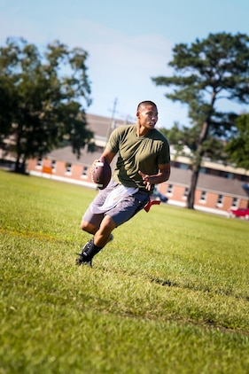 Training Noncommissioned Officer Cpl. Patrick Tep of Alexandria, Va., looks for an open receiver down field. Second Battalion, 8th Marine Regiment, 2nd Marine Division, gave their weathered camouflage utilities a week-long break to carry out a battalion size Olympics promoting unit cohesion and competitive spirits. The week kicked off with several events to include flag football, soccer, basketball, softball, Volleyball and a 5k run.
