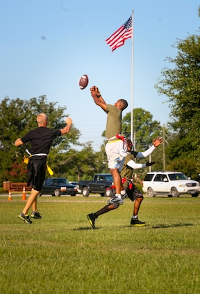 Marines and sailors with 2nd Battalion, 8th Marine Regiment, compete in a flag football game as part of the 2/8 Olympics. The unit gave their weathered camouflage utilities a week-long break to carry out a battalion size Olympics promoting unit cohesion and competitive spirits.